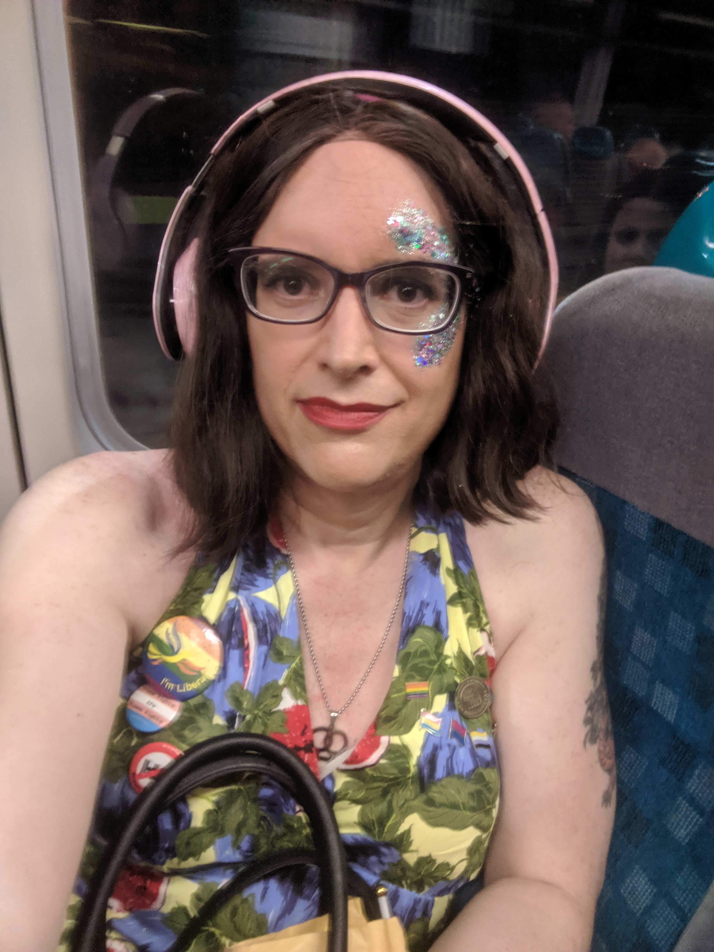 A selfie of me on the bus. I'm coming back from Cardiff Pride 2019. There's blue glitter painted on the right side of my face